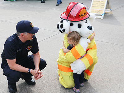 2019 Fire Department Open House, little girl hugging Sparky